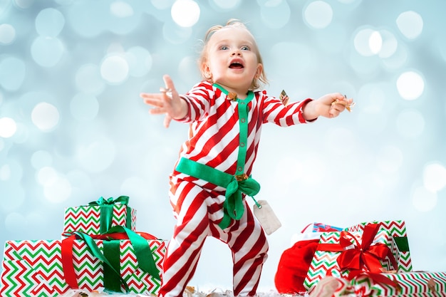 Cute baby girl 1 year old wearing santa hat posing over christmas
