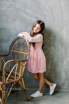 귀여운 아기 소녀 5-6 세 세련 된 핑크 드레스 overgrey 배경 입고. 카메라를 찾고 있습니다. 생일 파티. 축하.