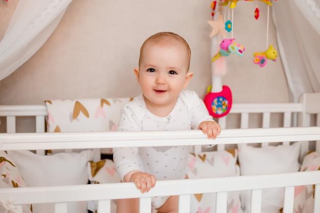 Милая девочка 8 месяцев сидит в детской кроватке дома