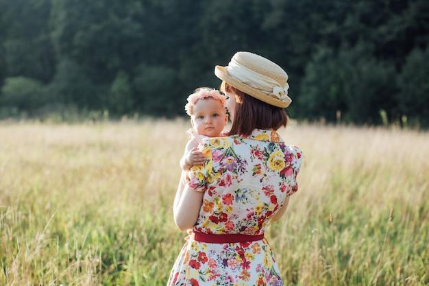Милая девочка и мама обнимаются в летнем поле. вид сзади красивая женщина-мать, держа ребенка на руках. маленькая дочь смотрит в камеру. счастливая семья, мама и дочь на поле