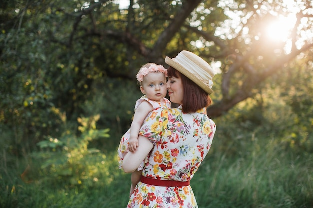 Милая девочка и мама обнимаются в летнем саду. вид сзади красивая женщина-мать, держа ребенка на руках. маленькая дочь смотрит в камеру. счастливая семья, мама и дочь на поле