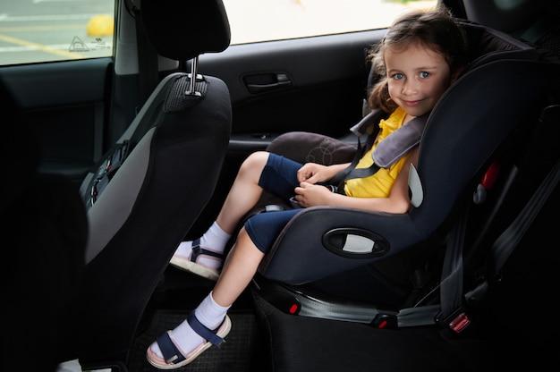 安全チャイルドシートに身を包んだかわいい女の赤ちゃんは、カメラを見ながら微笑む。チャイルドシートを使用して、車の中で子供と安全に旅行する