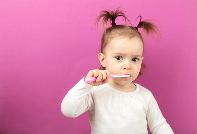 Милая девочка, чистящая зубы щеткой. вид сверху