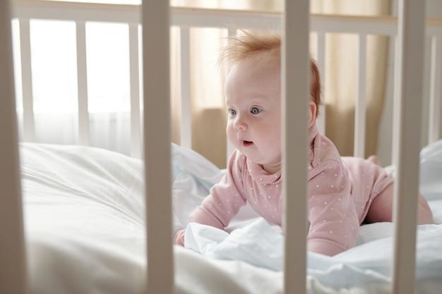 흰색 리넨에 으르렁거리는 귀여운 아기 소녀