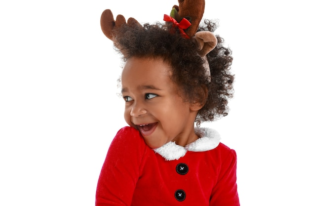 Cute baby girl dressed as santa on white surface