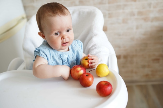 Cute baby girl eating apple in the kitchen.
