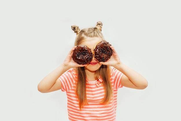밝은 배경에 달콤한 도넛을 먹는 귀여운 아기 소녀.