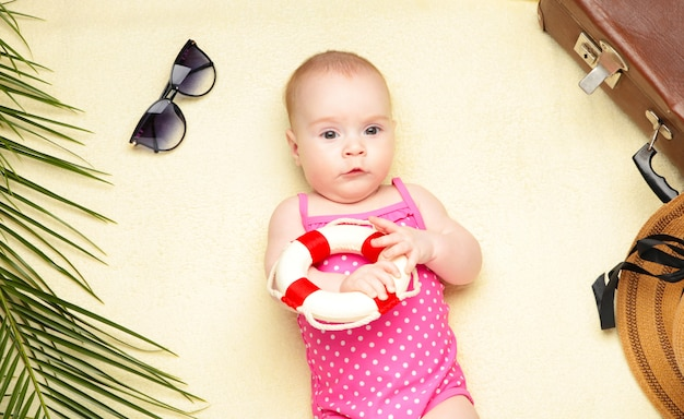 Cute baby girl holding lifebuoy on light background. holidays at sea with baby, summer concept