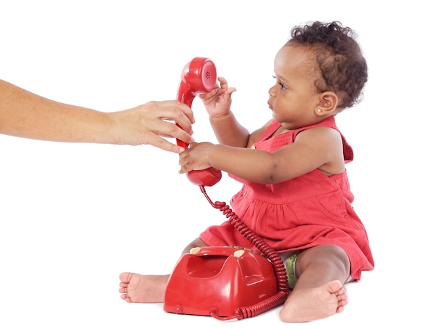 Cute baby girl holding a red phone