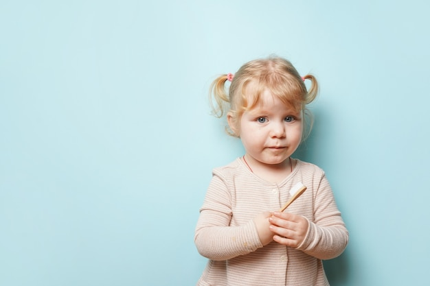 Cute baby girl holding toothbrush for brushing teeth on blue surface.