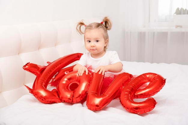 Cute baby girl holds the inscription love from balloons sits on white bedding.