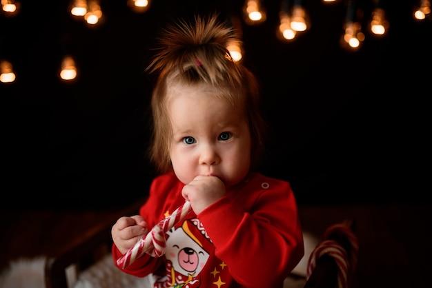 복고풍 garlands와 빨간 크리스마스 의상에서 귀여운 딸은 모피에 앉아