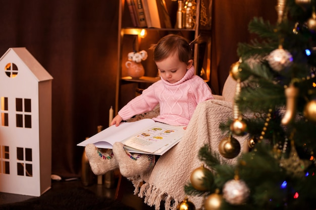 Милая девочка в свитере читает книгу в рождественском интерьере с огнями