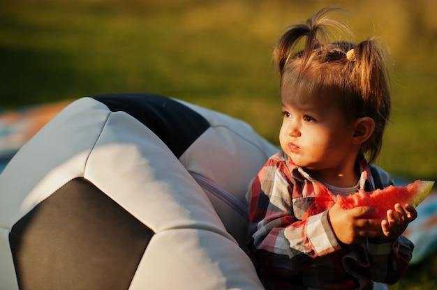 市松模様のシャツを着たかわいい女の赤ちゃんは、サッカーボールのプフに座ってスイカを食べます。