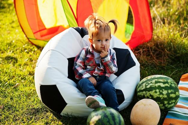 市松模様のシャツを着たかわいい女の赤ちゃんは、スイカとサッカーボールのプーフに座っています。