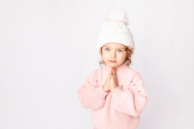 Милая девочка в розовой зимней одежде на белом фоне, место для текста