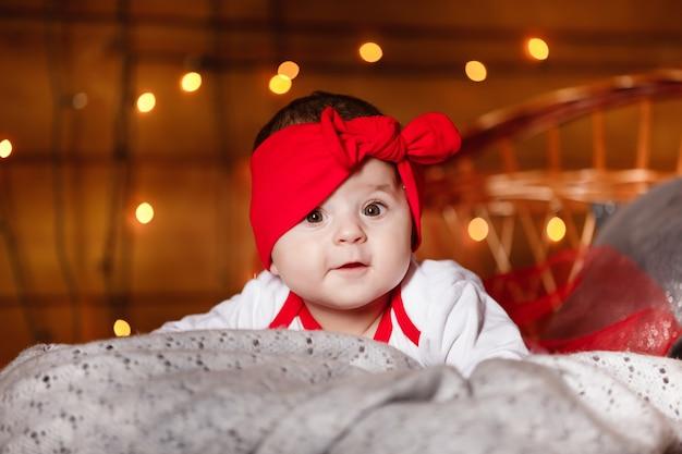 Милая девочка в красном банте на голове и белом свитере, лежащем на одеяле, новогодний фон в студии с рождественскими пейзажами.