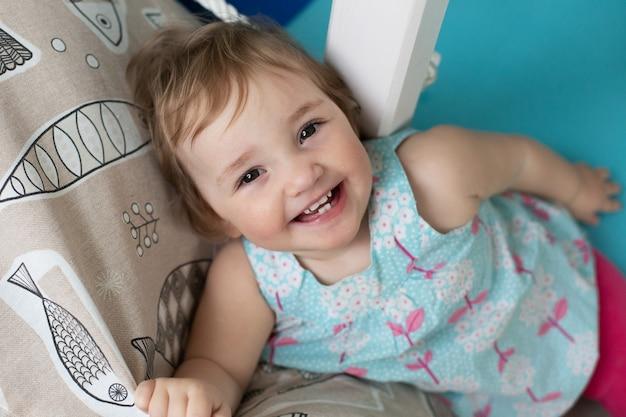 キッズルームに横たわって笑っているかわいい女の赤ちゃん。のんきな子供時代。