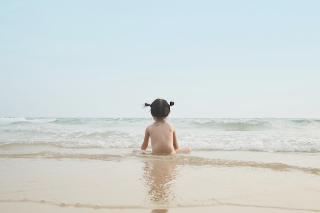 Cute baby girl looking forward to the sea