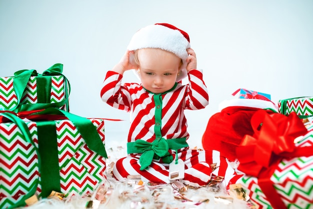Cute baby girl near santa hat posing over christmas background with decoration. sitting on floor with christmas ball.