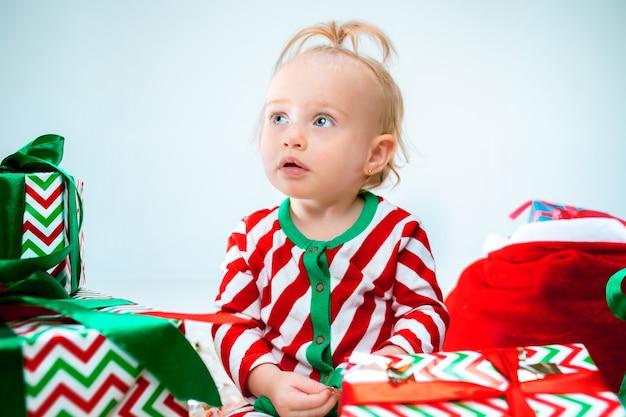 크리스마스 배경 위에 포즈 산타 모자 근처 귀여운 아기 소녀. 크리스마스 공을 바닥에 앉아. 휴가 시즌.