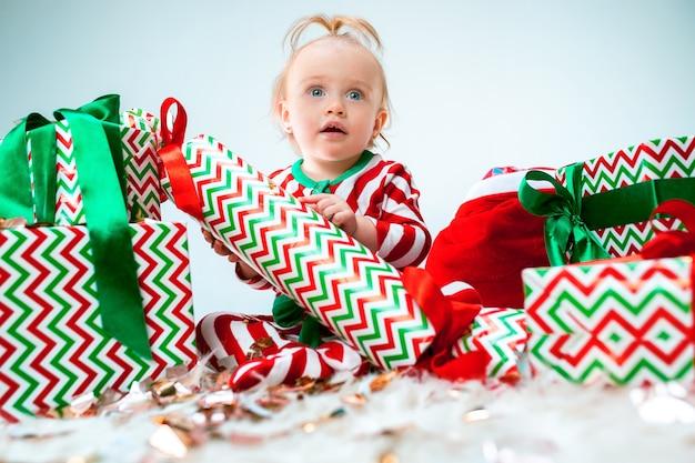 장식으로 크리스마스 배경 위에 포즈 산타 모자 근처 귀여운 아기 소녀. 크리스마스 공을 바닥에 앉아. 휴가 시즌.