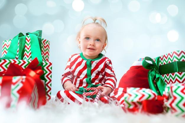 장식으로 크리스마스 배경 위에 포즈 산타 모자 근처 귀여운 아기 소녀. 크리스마스 공을 바닥에 앉아.