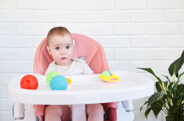 Cute baby girl playing a rattle in chair. top view