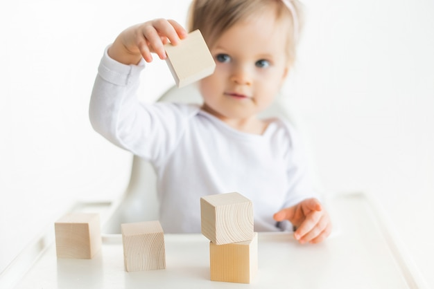 Cute baby girl playing with wooden cubes. little child building tower. construction block for kids. montessori educational method. selective focus