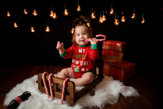 Cute baby girl in a red christmas costume with retro garlands sits on a fur