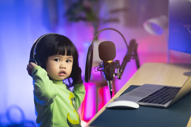 自宅のレコーディングスタジオでマイクを使って新しい曲を録音するヘッドフォンで歌うかわいい女の赤ちゃん