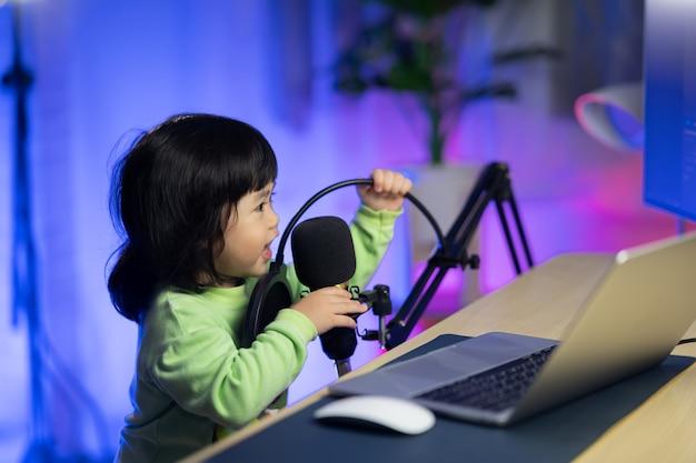 Милая девочка поет в наушниках, записывает новую песню с микрофоном в домашней студии звукозаписи
