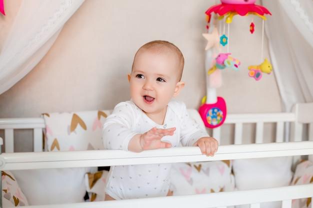 Милая девочка сидит в детской кровати дома