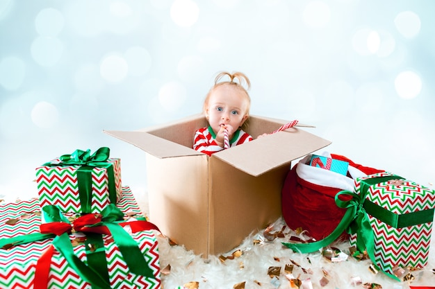 Cute baby girl sitting in box over christmas background. holiday, celebration, kid concept