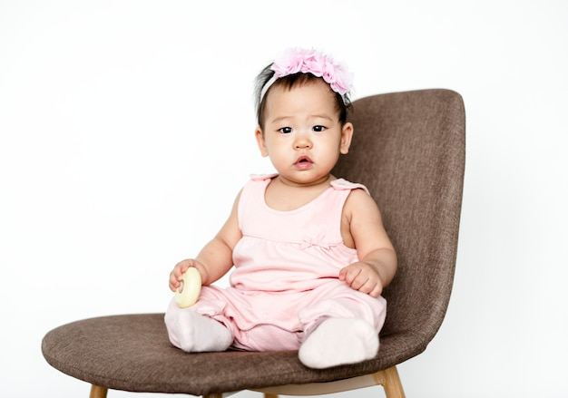 Cute baby girl sitting on a chair