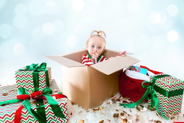 クリスマスの背景の上のボックスに座っているかわいい女の赤ちゃん。休日、お祝い、子供の概念