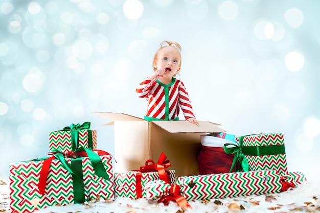 Милая девочка сидит в коробке на фоне рождества. праздник, праздник, детская концепция