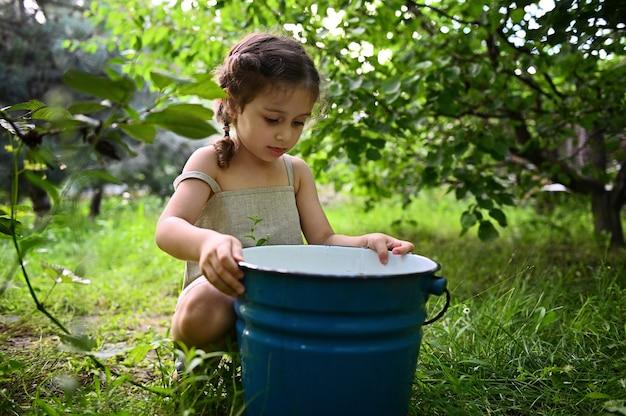 庭に座って金属製のバケツをのぞくかわいい女の赤ちゃん。園芸