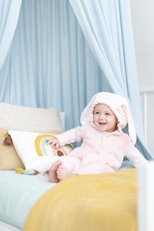 그녀의 침대에 앉아 귀여운 아기 소녀 무료 사진