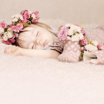 Милая девочка спит с цветами