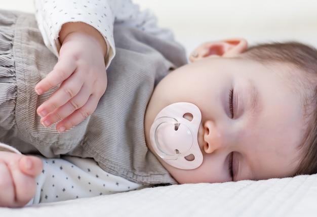 흰색 침대 커버 위에 자는 귀여운 아기 소녀