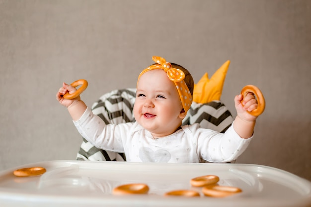 Cute baby girl smiles sitting in a baby chair and eating bagels