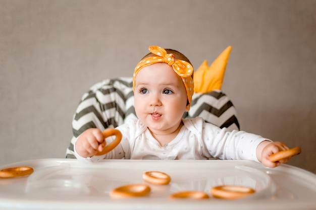 귀여운 아기 소녀 미소 아기 의자에 앉아 베이글을 먹는