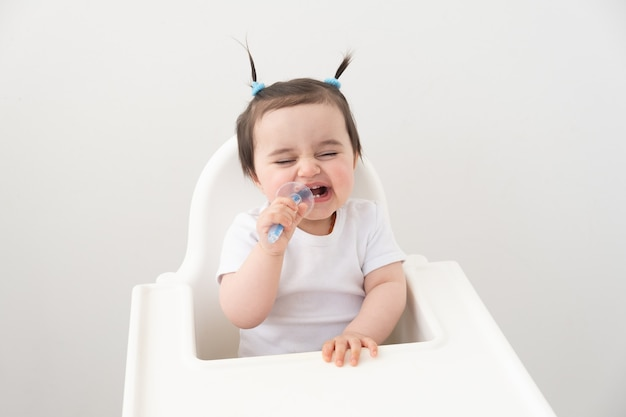 Cute baby girl smiling and brushing her teeth with a colored brush