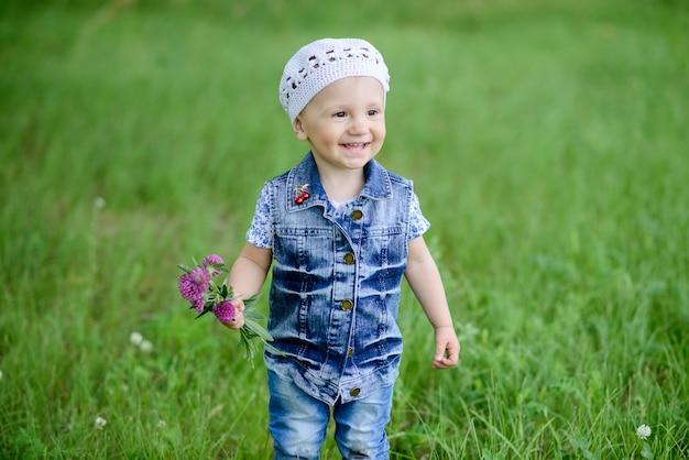 Милая девочка гуляет в красивом парке с красочным цветком в летний сезон, он улыбается и счастлив, стоя на открытом воздухе.