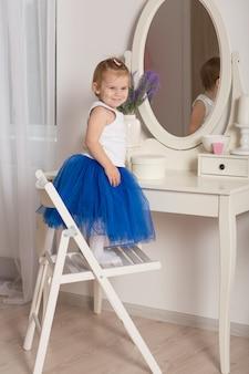 丸い鏡と白い寝室で彼女の反射を見ているかわいい女の子