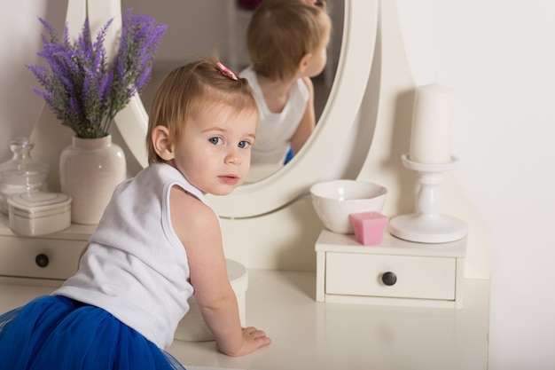 Cute baby girl watching her reflection in a white bedroom with a round mirror