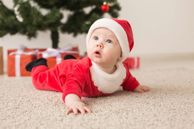 Cute baby girl wearing santa claus suit crawling on floor over christmas tree.