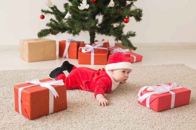 Cute baby girl wearing santa claus suit crawling on floor over christmas tree