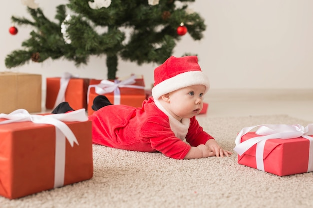 Cute baby girl wearing santa claus suit crawling on floor next to christmas tree